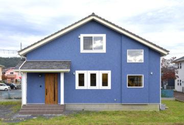 青い外壁の三角屋根の家。